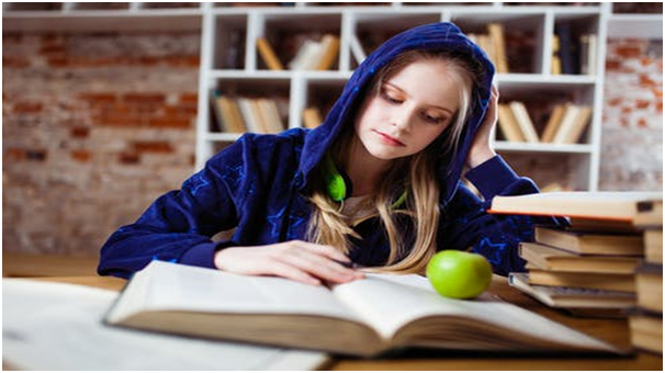 A female student engrossed in her studies at a library.