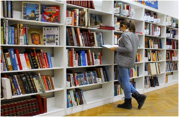 A female students browsing books at a library.